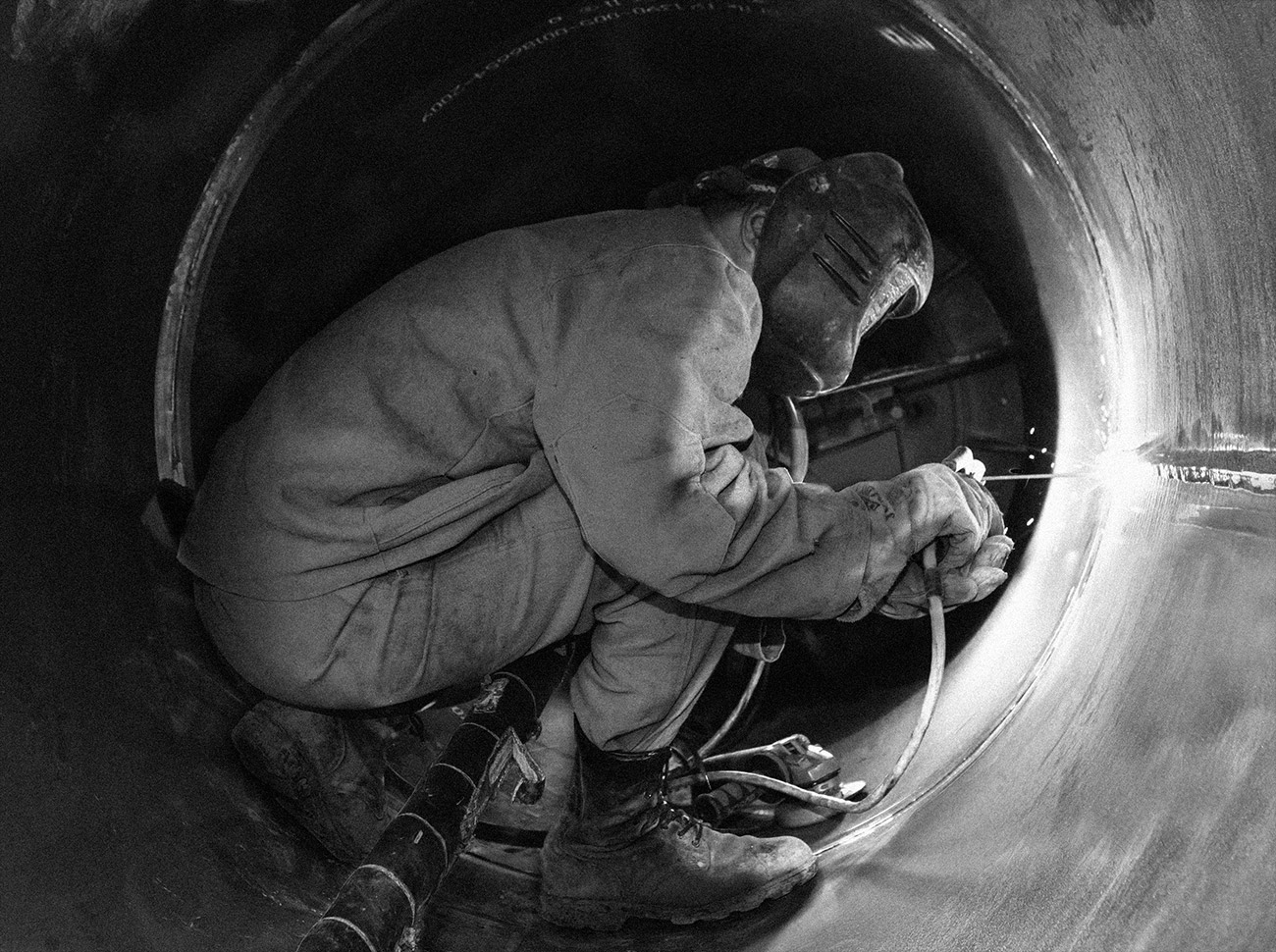Worker welding a pipeline in Siberia